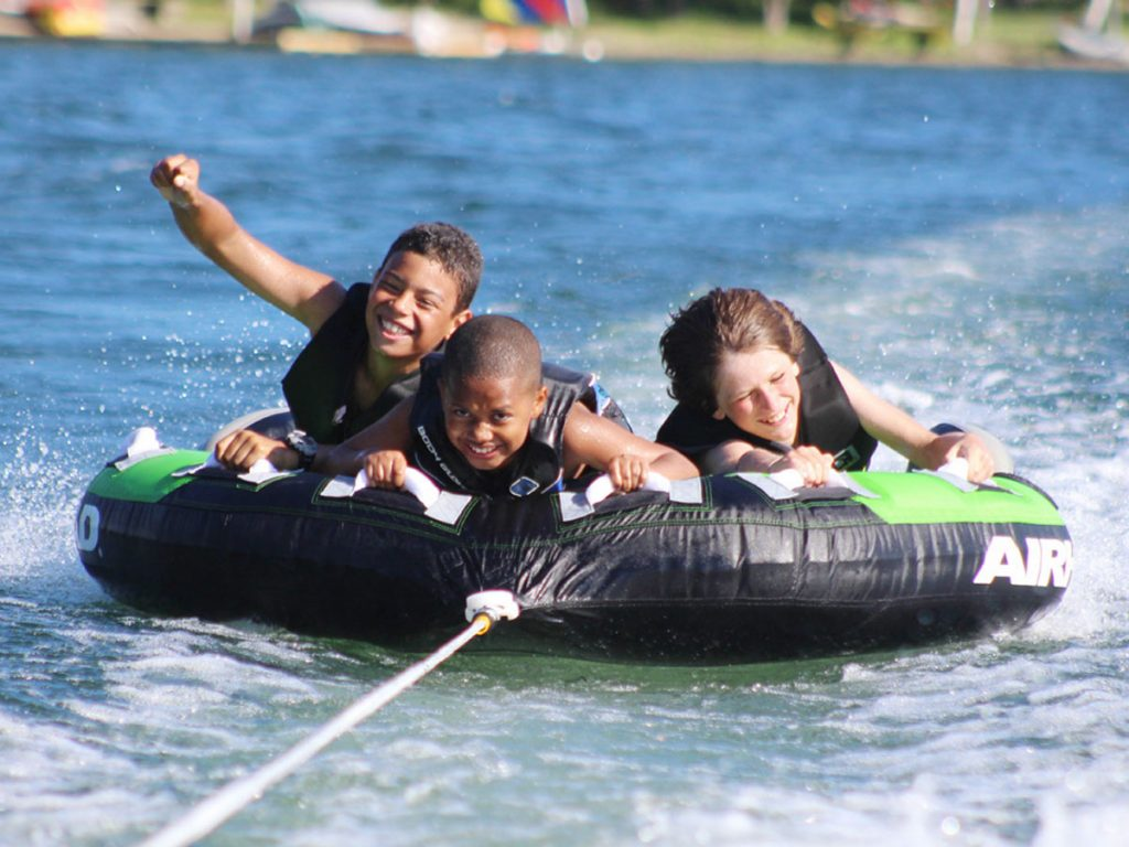 Three youngsters ride on a water tube at Camp Dunnabeck