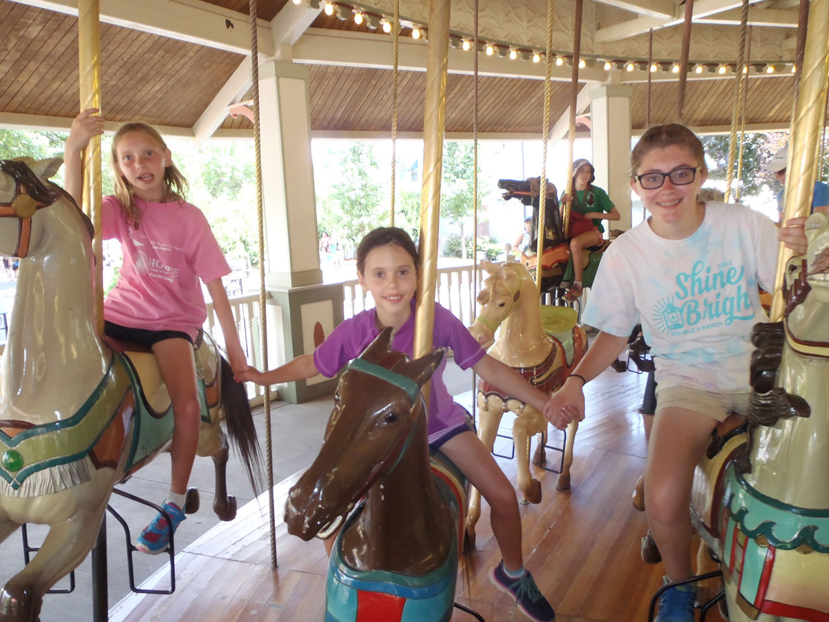 three female campers from Camp dunnabeck ride hand in hand on horses on a carousel ride