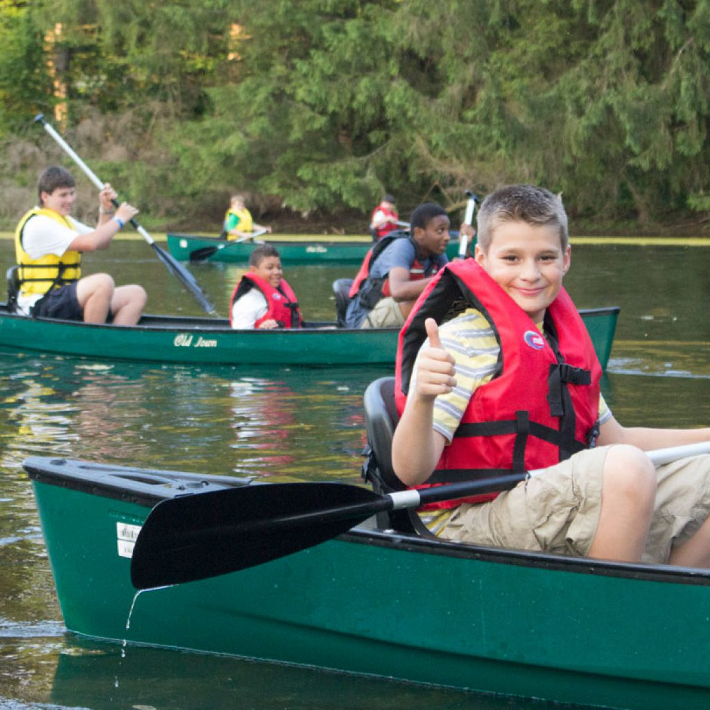 Boy in green canoe gives the thumbs up with resting on pond at camp dunnabeck
