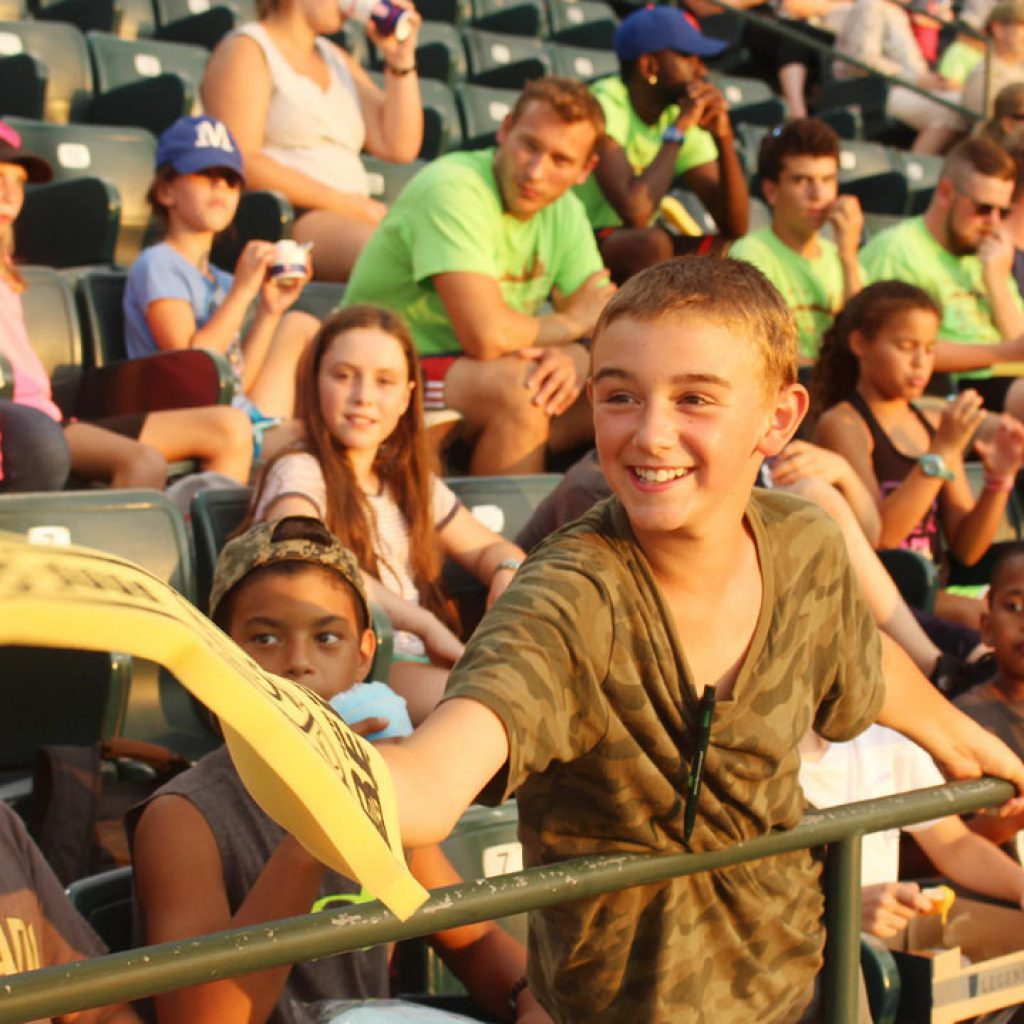 Boy at camp dunnabeck reaches out with foam finger at a baseball game off camp