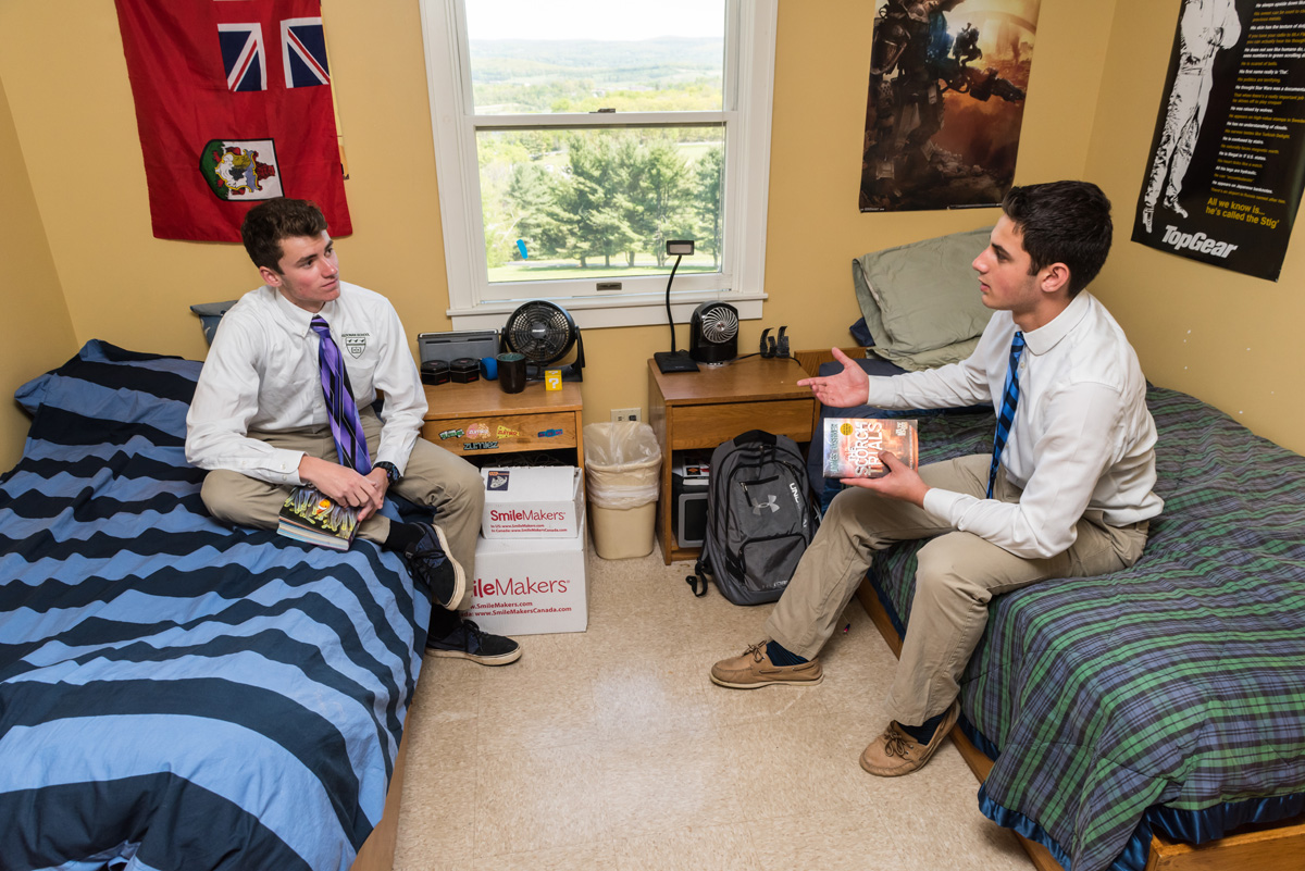 Two teen boys sit on beds in their dorm room at Kildonan