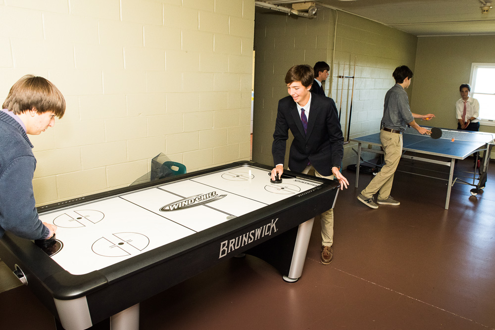 Two teen boys play table hockey in the foreground, two more play table tennis behind. Goldman Hall, The Kildonan School