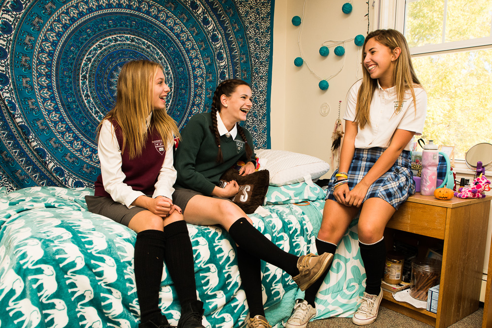three teen girls sit in dorm room wearing school uniforms