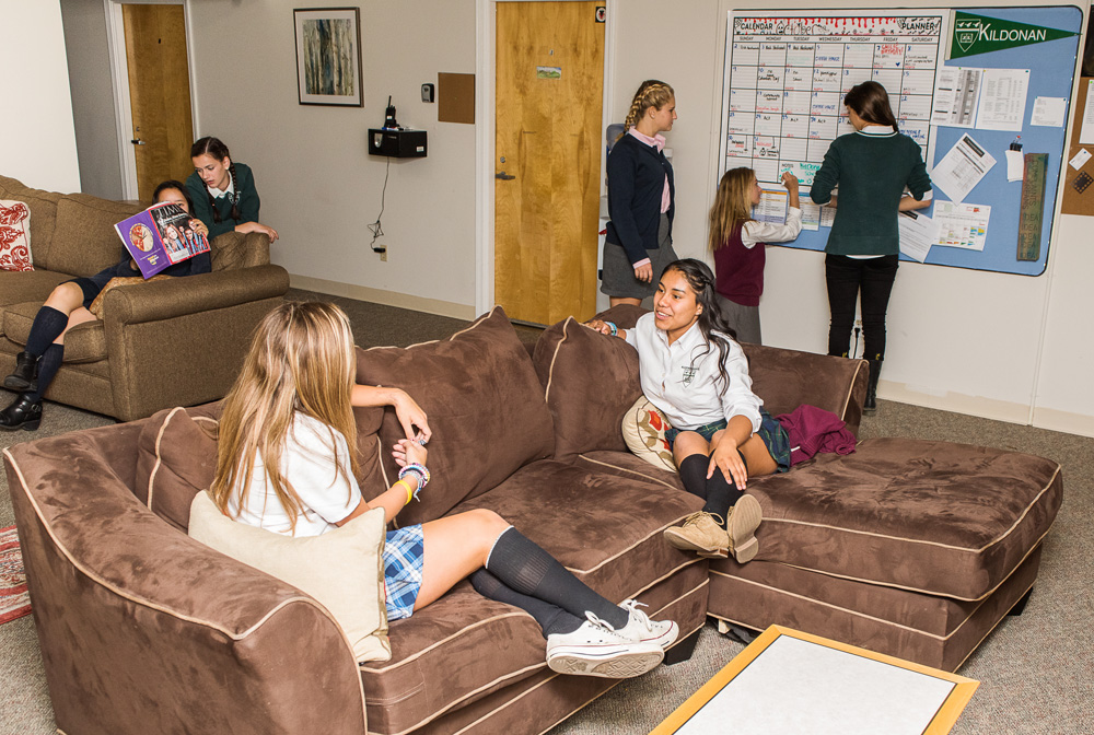 Girls sit on brown couch in lounge area of dorm