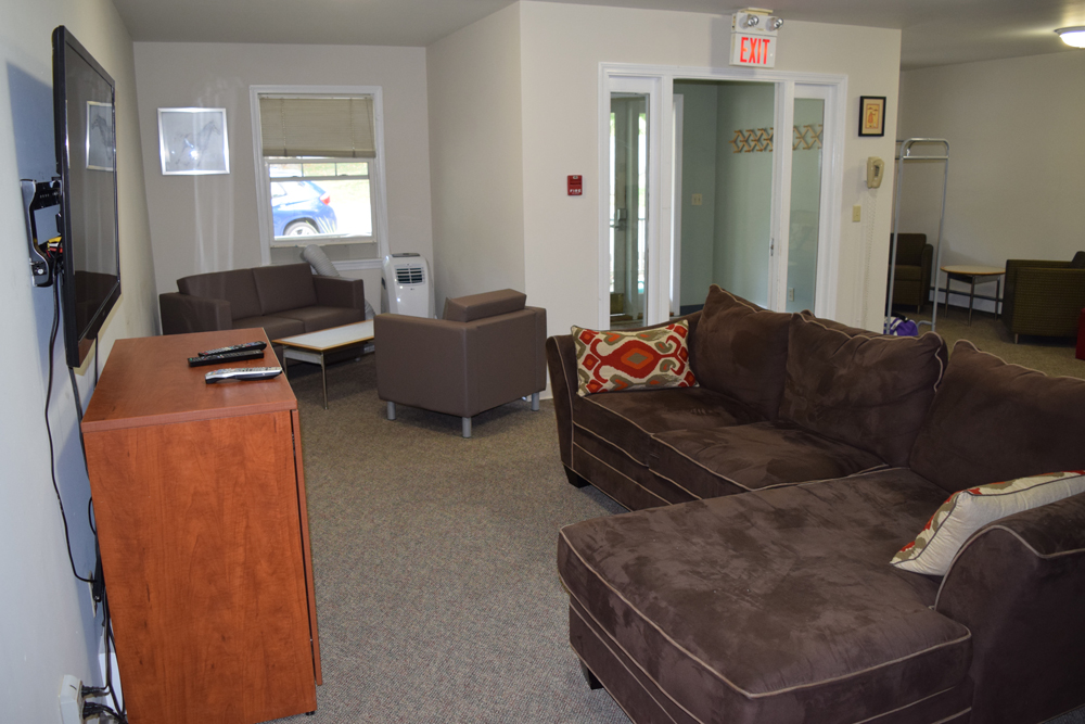 Empty dorm lounge with brown couch and tv with cabinet