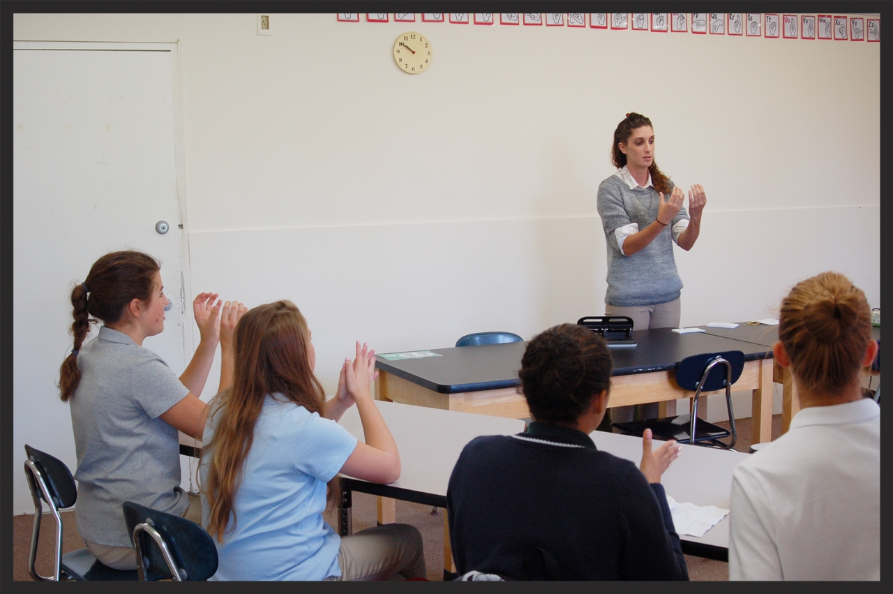 Female teacher shows class how to make signs in American Sign Language class.