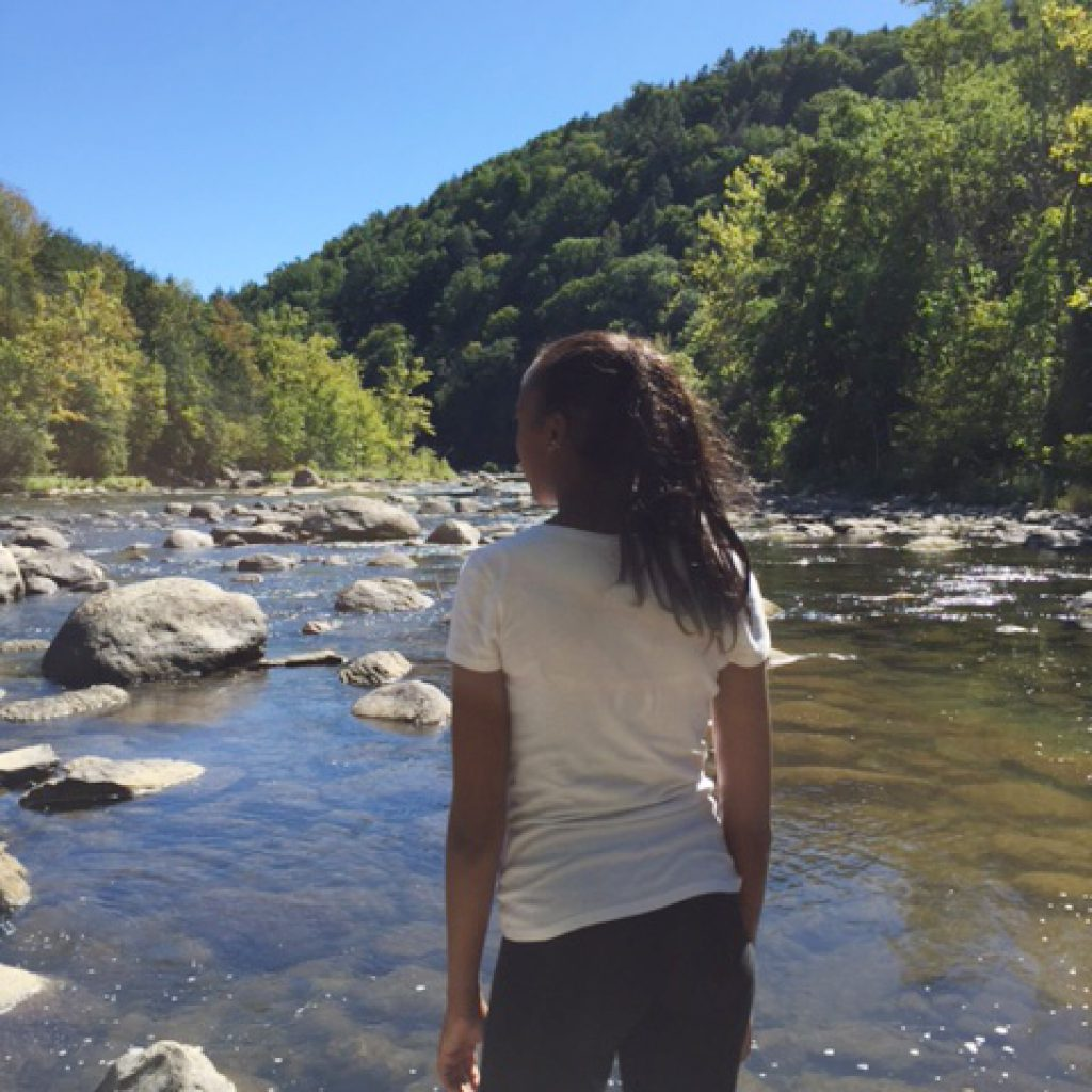 Teenage girl looking out over mountain stream