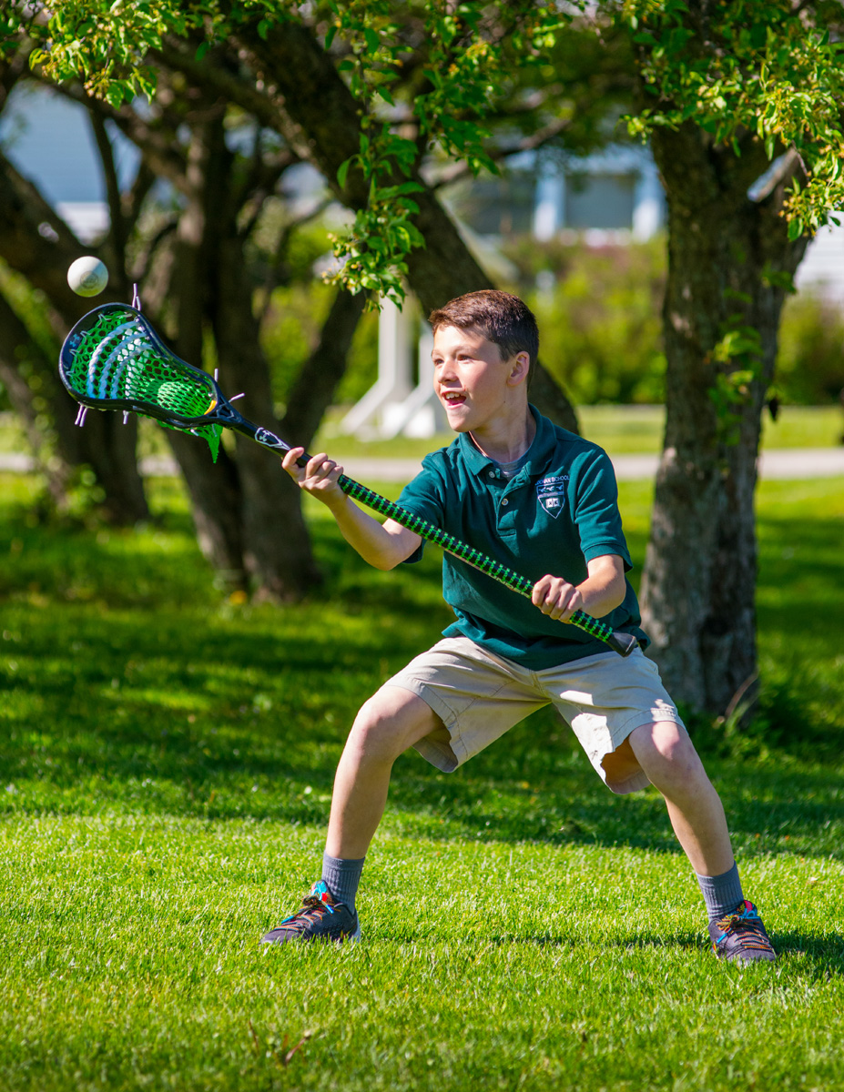 Young male student in green shirt practices a lacrosse catch. Green lawn at the Kildonan School.