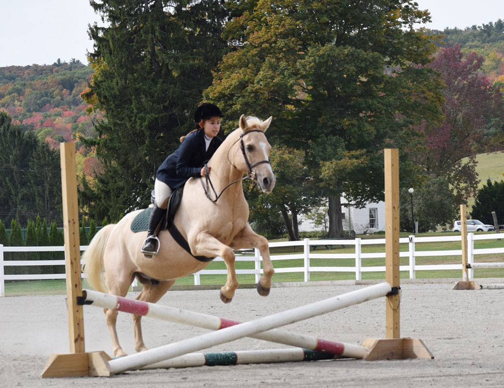 Kildonan student on tan horse jumps over crossed bar jump in riding ring