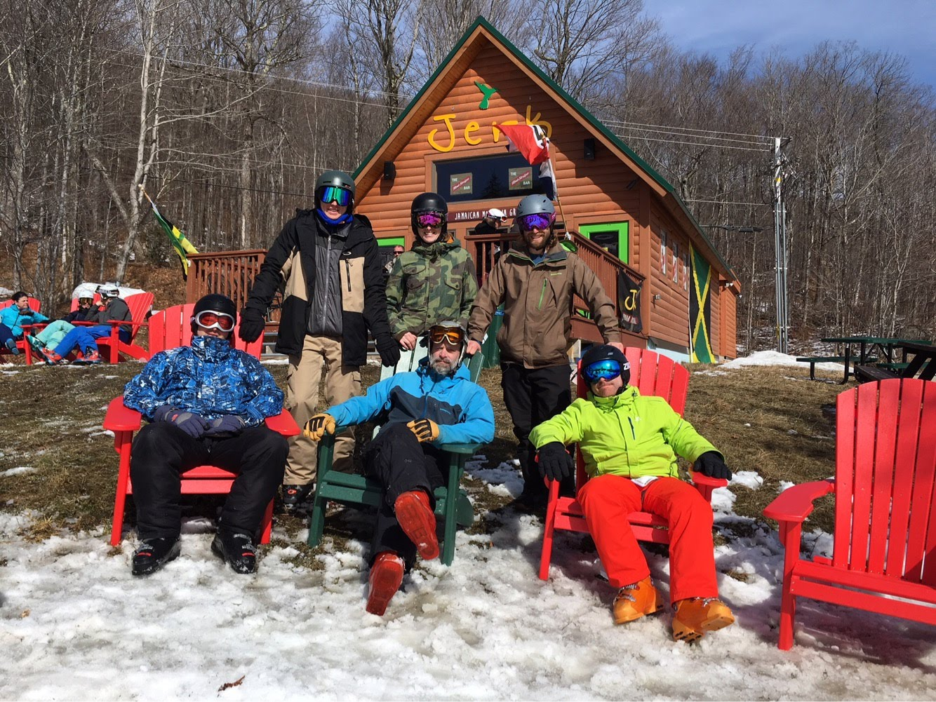 Skiers and snowboarders rest in front of restaurant