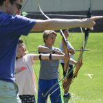 Instructor and campers practice archery skills at Camp Dunnabeck.