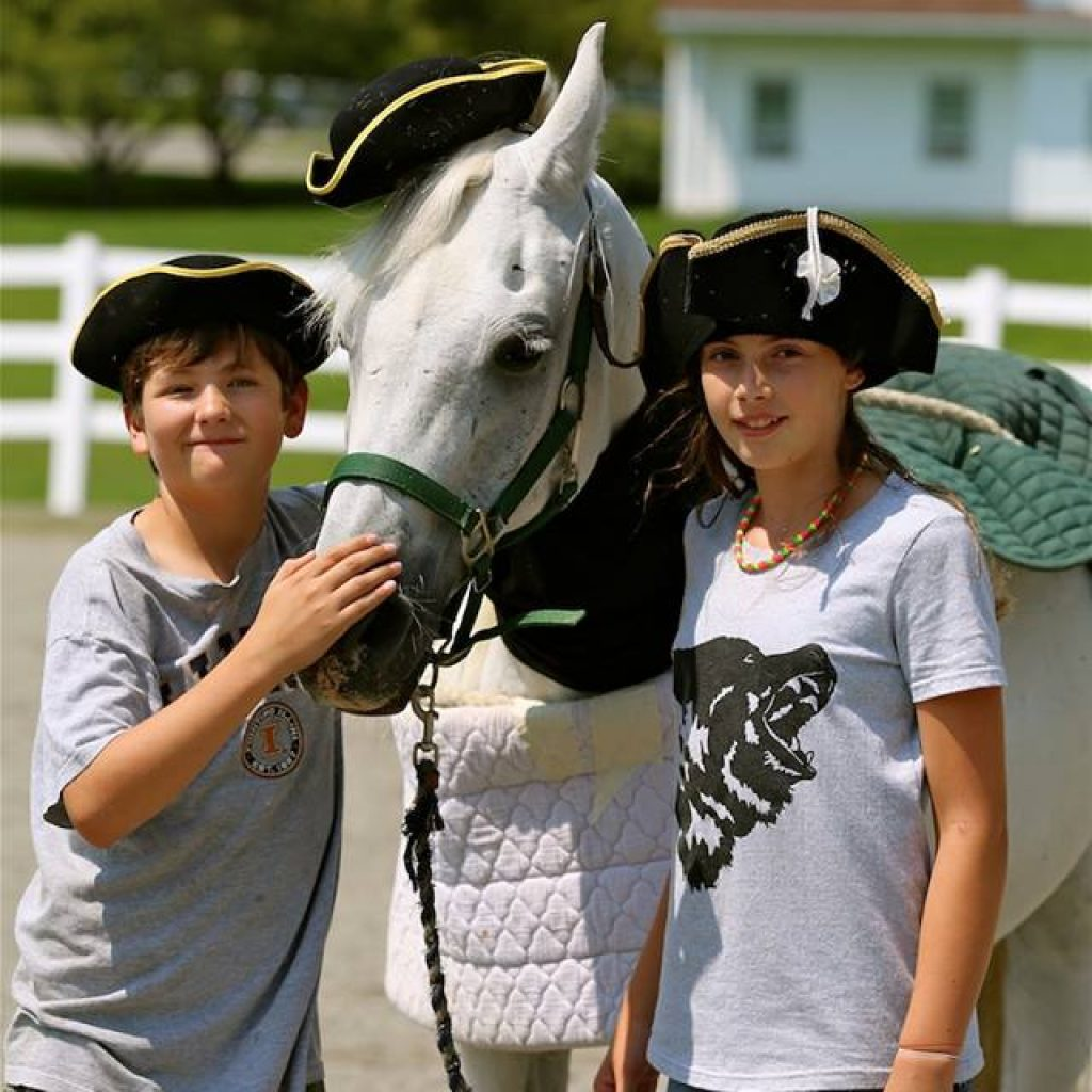 Two Camp Dunnabeck campers pose with a white horse. All have pirate hats on.