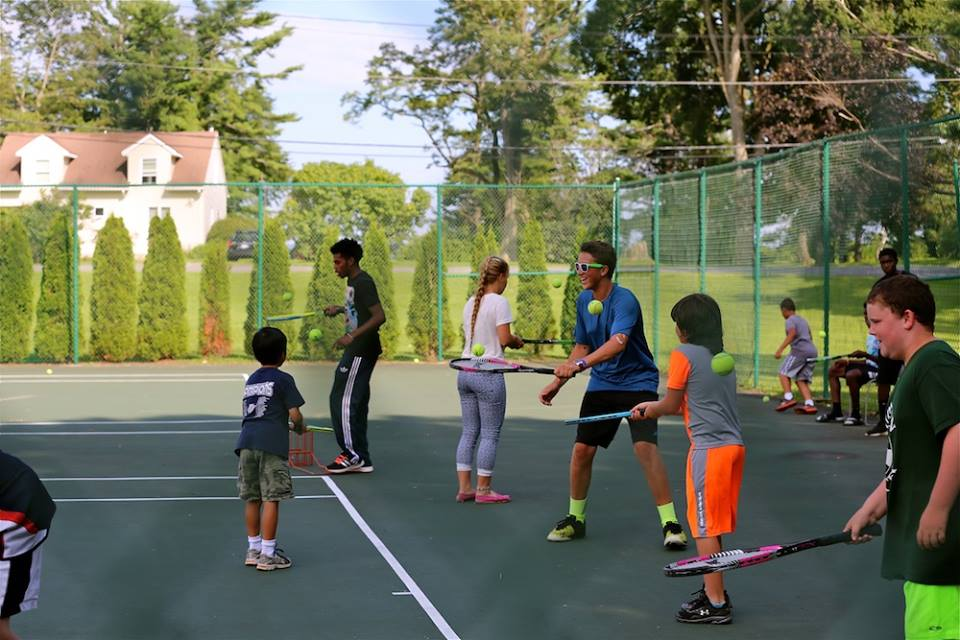 Group of Camp Dunnabeck campers bounce tennis balls on rackets on outdoor court.