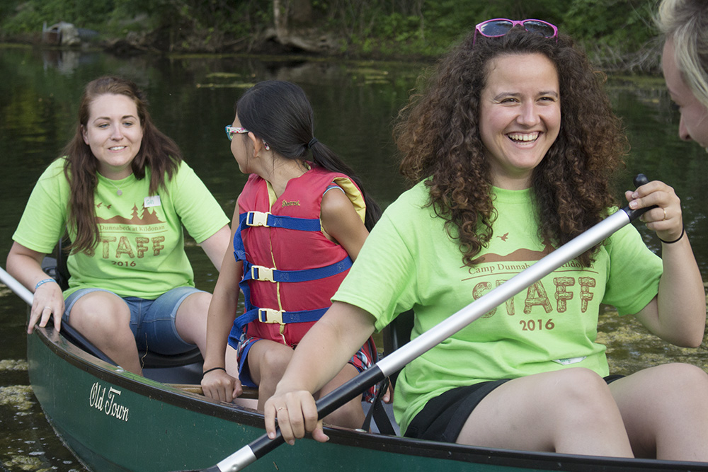 Two camp counselors paddle canoe with camper in middle of boat.