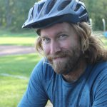Male teacher with bike helmet smiles at camera after mountain biking.