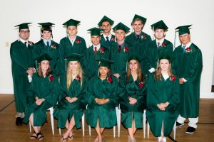 Group of graduating high schoolers in green caps and gowns.