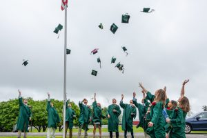 Dyslexic Kildonan graduates in green robes throw caps into the air.