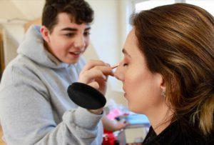 Young man applies make up to a woman's face
