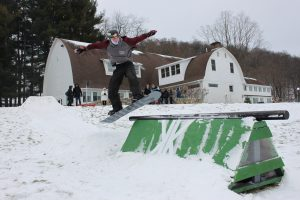 Young man on a snowboard leaps onto a rail held positioned on a triangular frame.