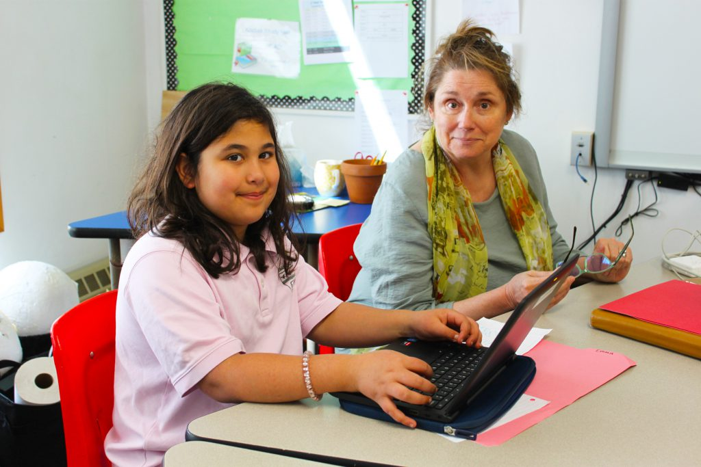 Young female student works side by side with her teacher.