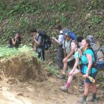 Group with backpacks hike on dirt trail in costa rica