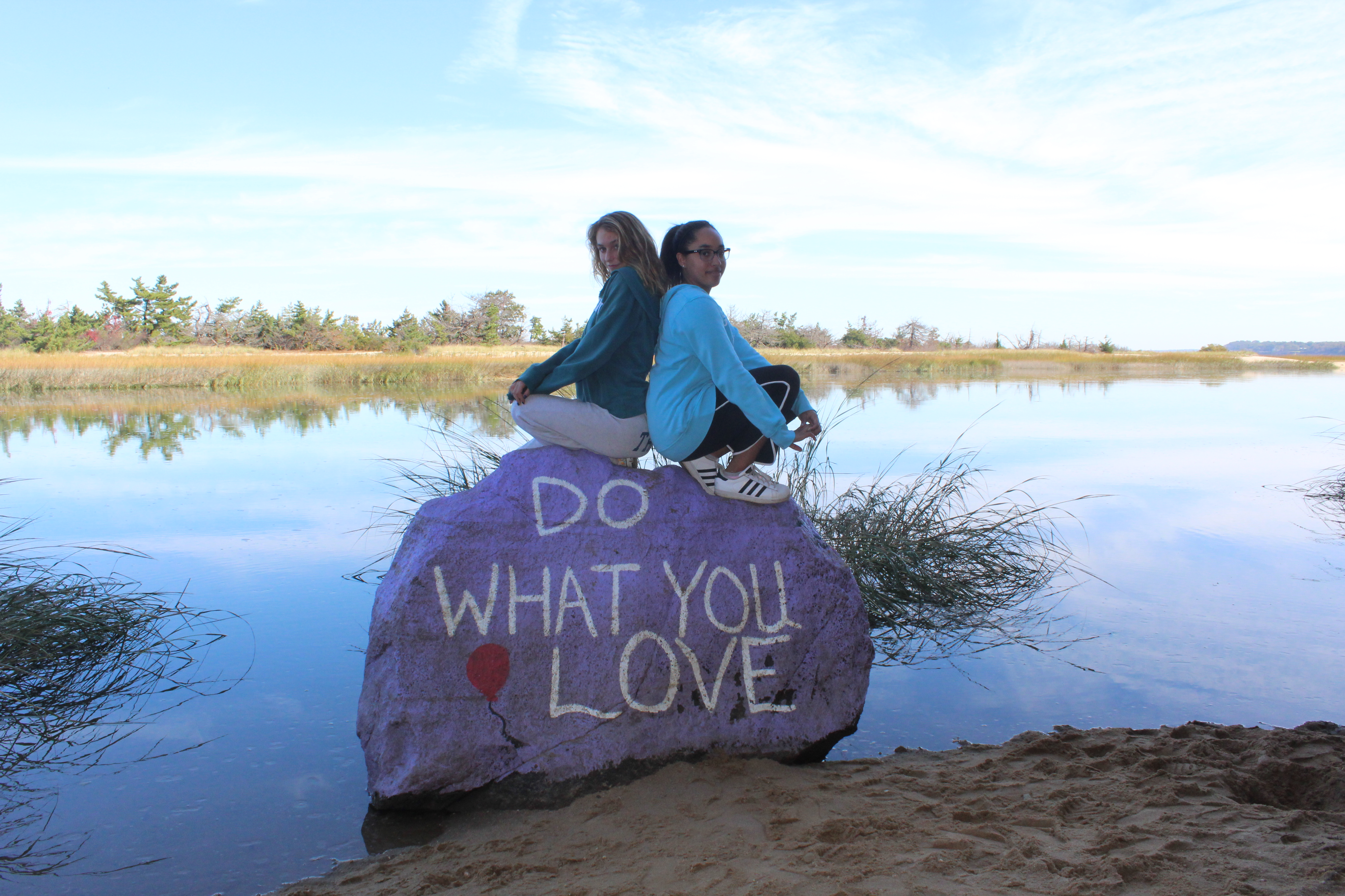 "Two teenage girls on rock near lake, rock reads ""Do what you love"""