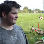 Teenage male mountain bike racer post race, looks off to the side.