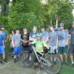 Mountain bike racing team photo, group is post-race and dirty.