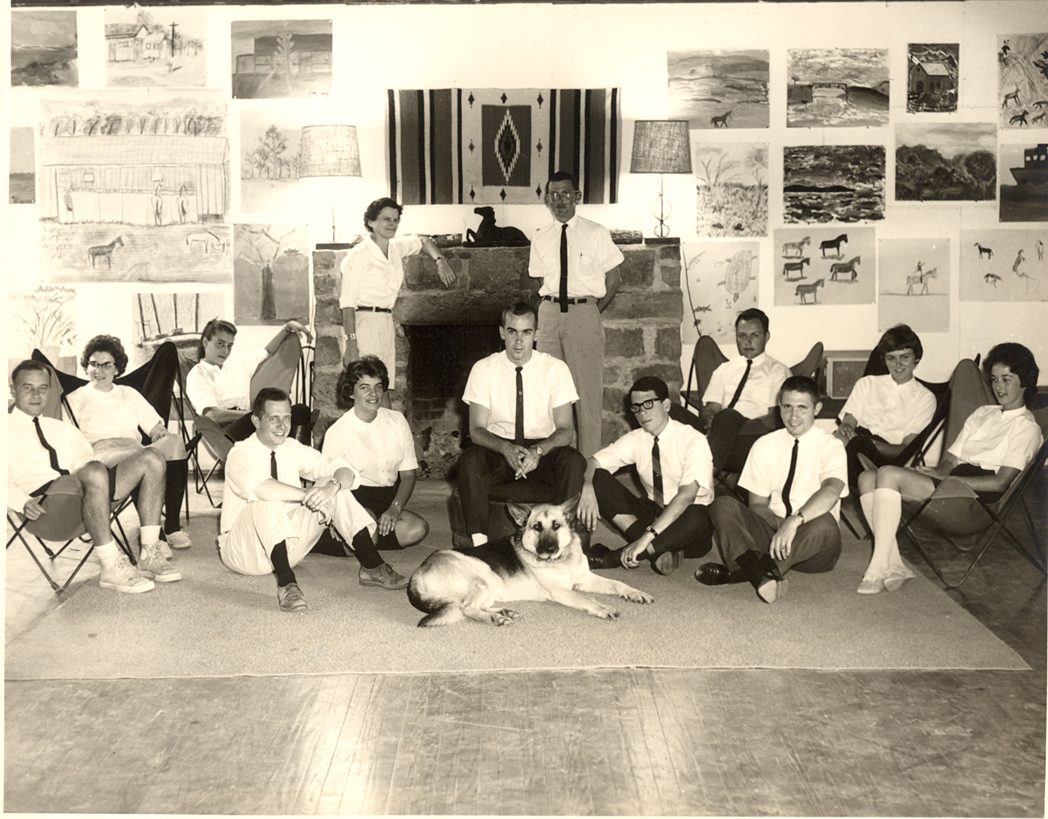 Black and white photo of teachers in shirt and tie at Camp Dunnabeck, german shepherd in front.