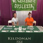 "Two female students sit at table with Kildonan School banner and ""We Celebrate Dyslexia"" sign."
