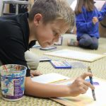 Elementary art student painting on floor with watercolors.