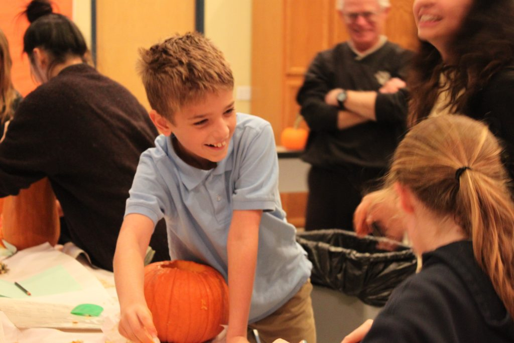 Kildonan student smiling at another student while carving his pumpkin