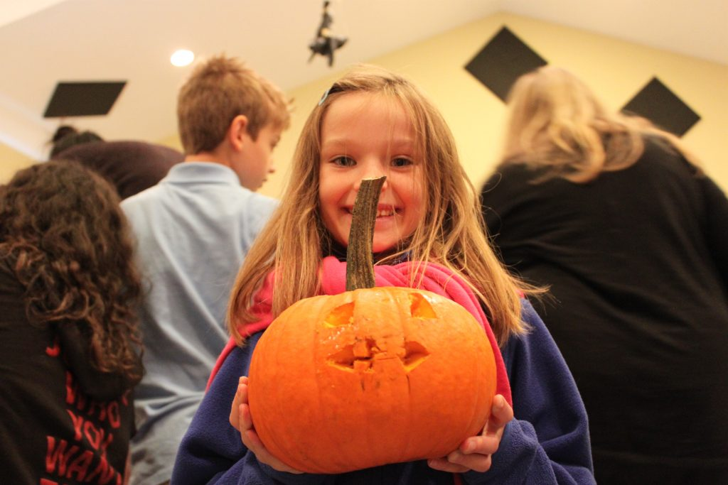 Kildonan elementry student smiling and holds up her carved pumpkin