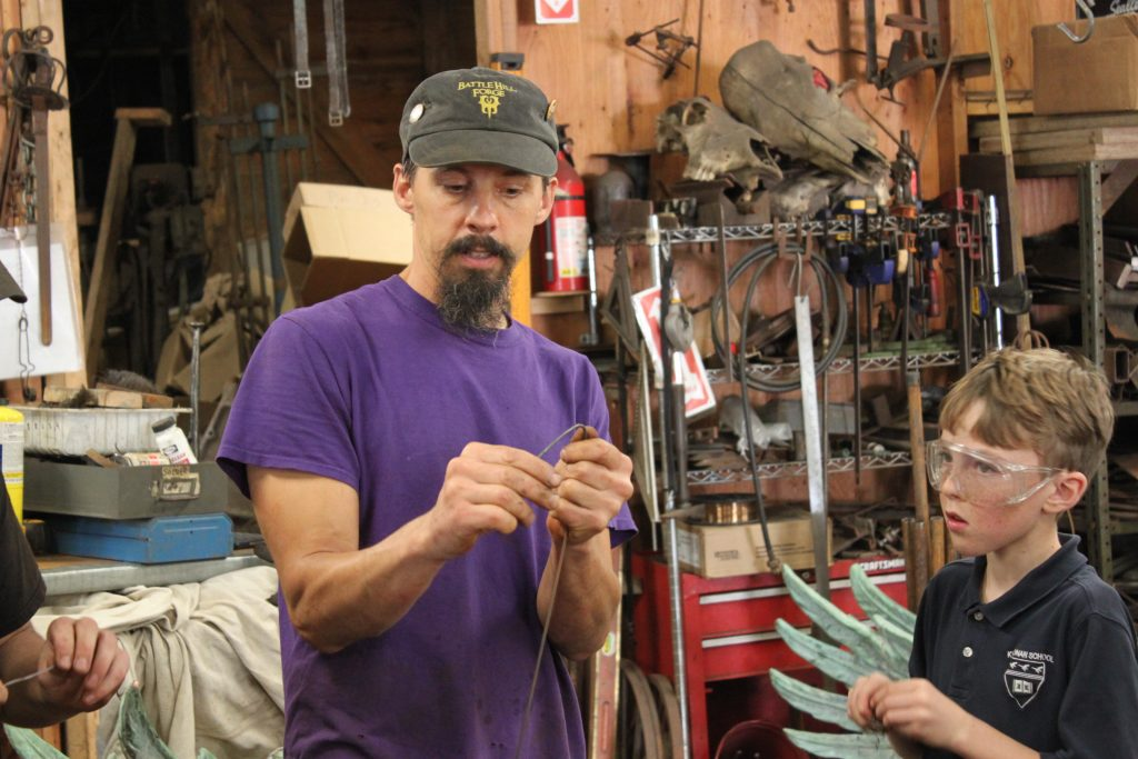 Metal works instructor teaching a Kildonan student to bend metal wire in studio.