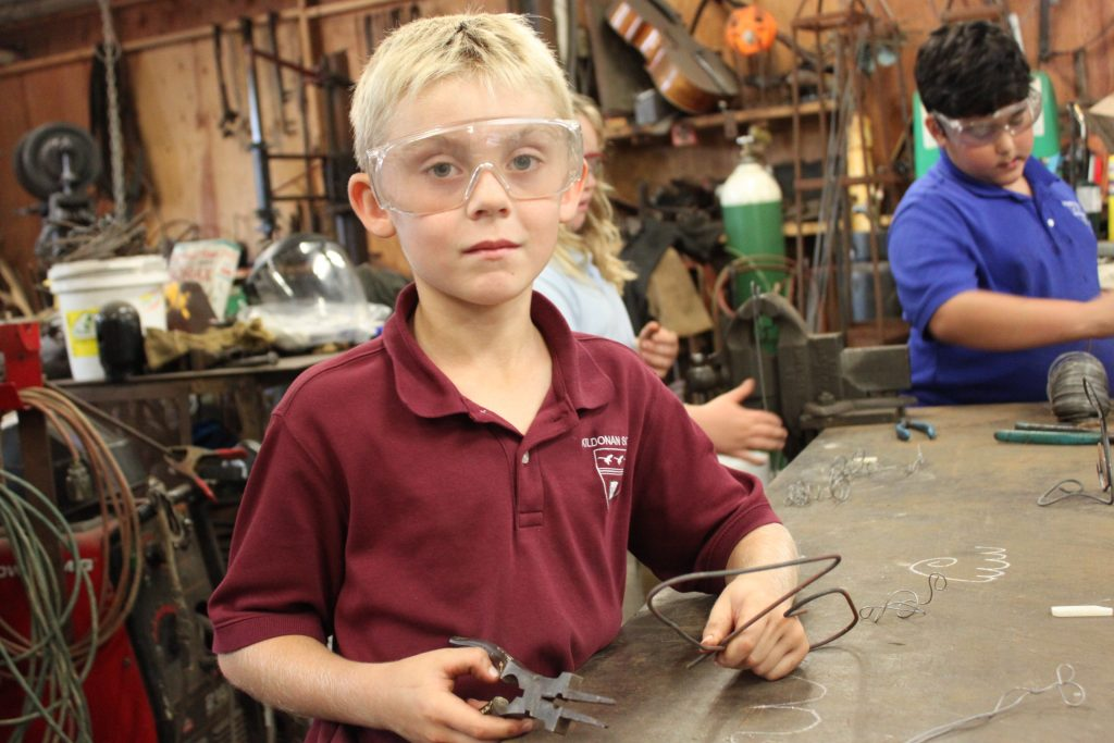 Young Kildonan boy bending metal wire wearing safety glasses.