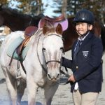 Equestrian: Kildonan student in suit and helmet posing with white horse.