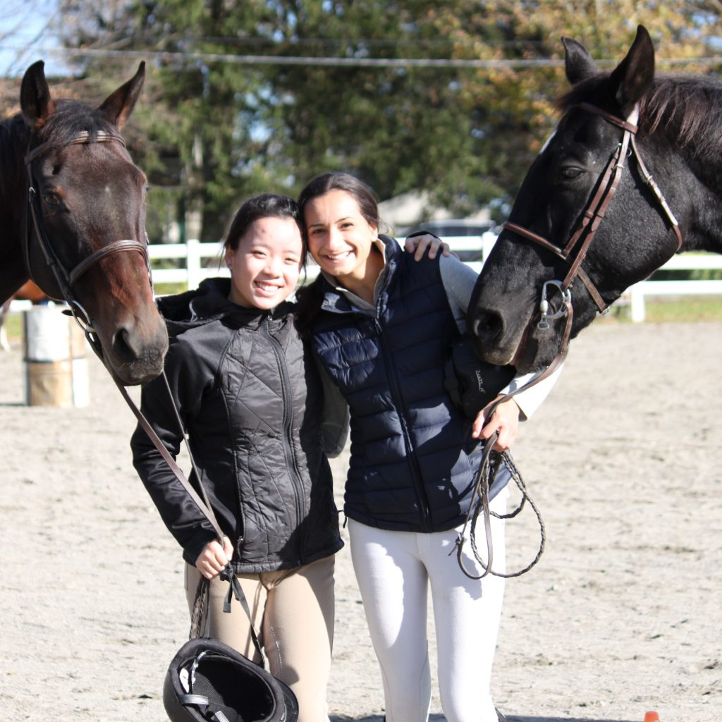 Two females equestrian students posing with horses