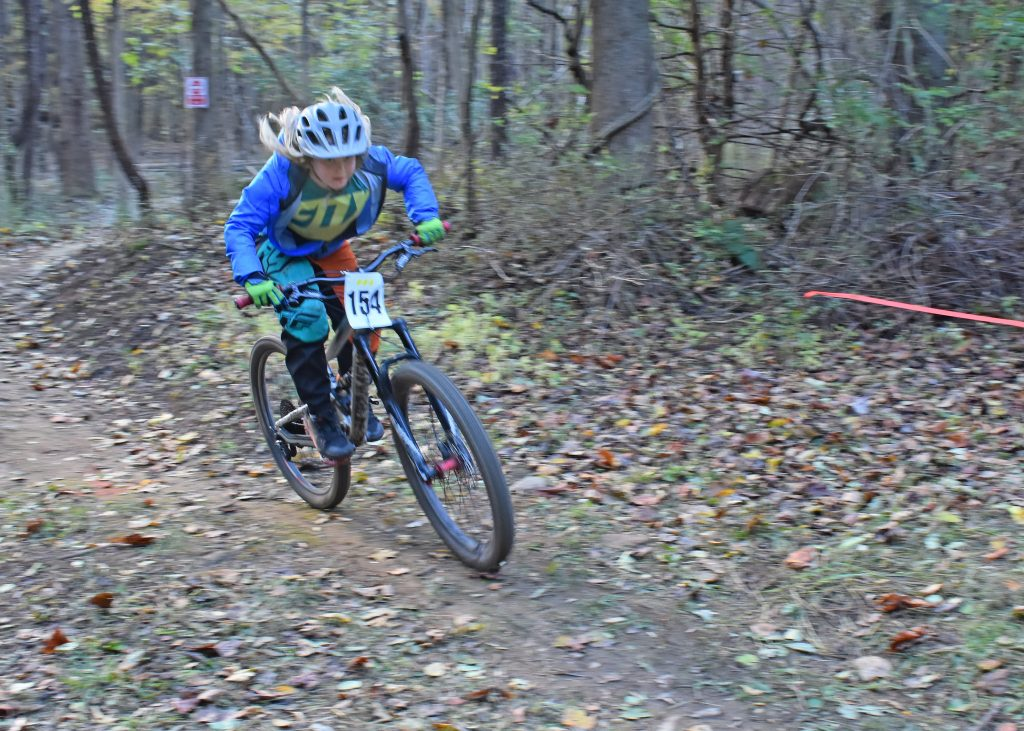Kildonan Mountain biking, student racing through woods, photo blurred.