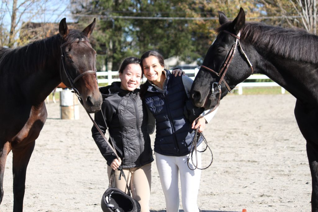 Two females students from Kildonan posing with horses