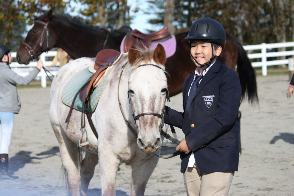 Kildonan student in suit and helmet posing with white horse