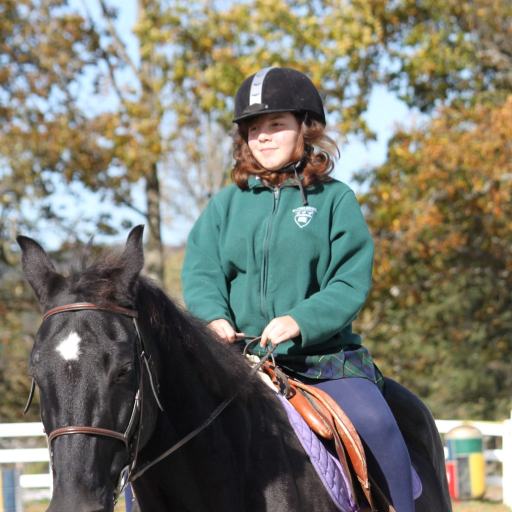 Female equestrian student riding a black horse