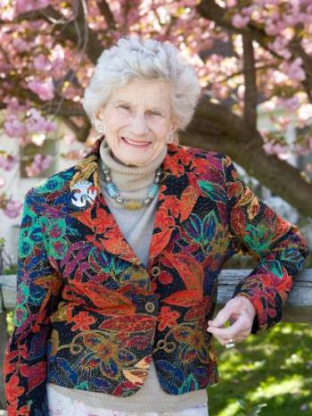 Older woman with colorful blazer and chunky necklace stands in front of cherry blossoms.