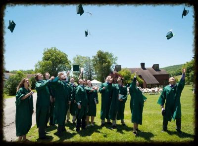Kildonan graduates in green robes toss hats after graduation.