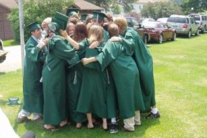 Group of Kildonan graduates in green robes huddle and hug.