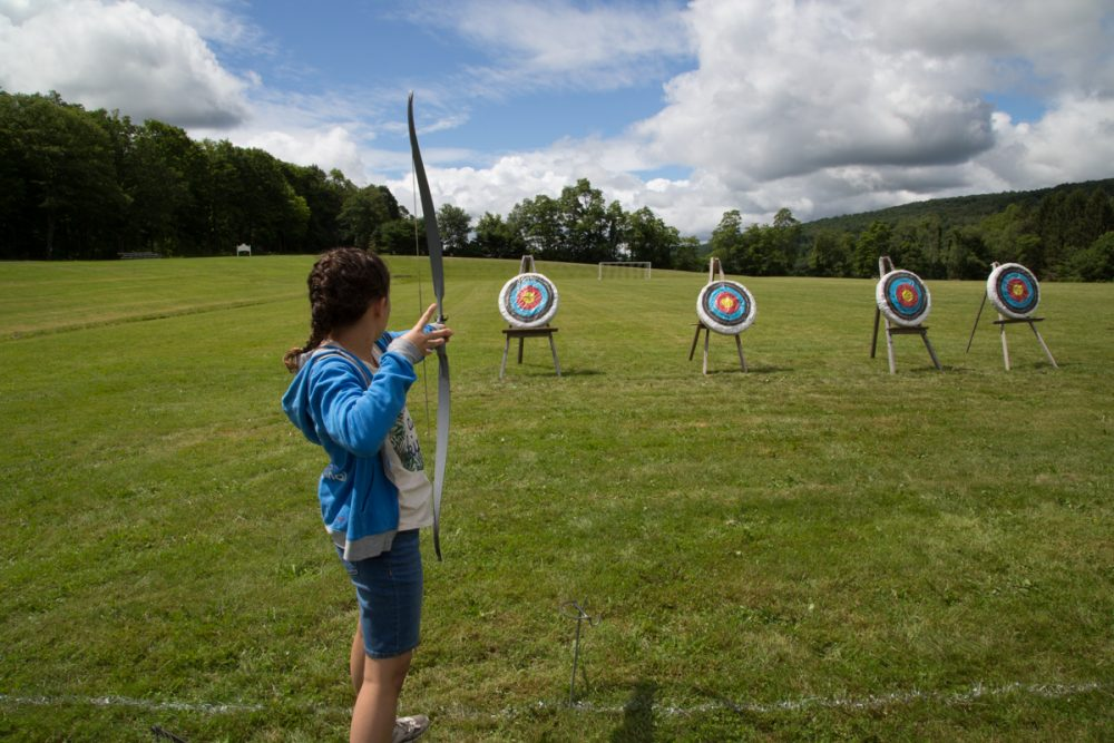 Female camp dunnabeck camper takes aim at an archery target, one of three set out in a grassy field.