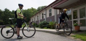 Camp dunnabeck biking instructor stands on left with bike as camper descends step on right outside athletic center building