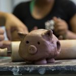A small clay pig sits on a paint-splotted table, Camp Dunnabeck campers are blurred in the background