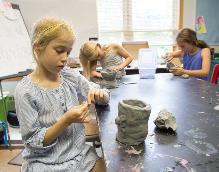 Three Camp Dunnabeck girls sit around a paint-splattered table making clay sculptures. Girl in foreground wears grey dress and makes a vase