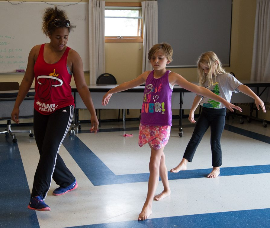 Two young female Camp Dunnabeck campers follow their counselor through dance routine.