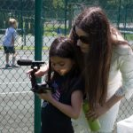 Camp Dunnabeck filmmaking instructor helps young female camper line up video camera.